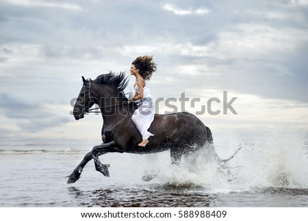 Beautiful woman with horse riding on the sea
