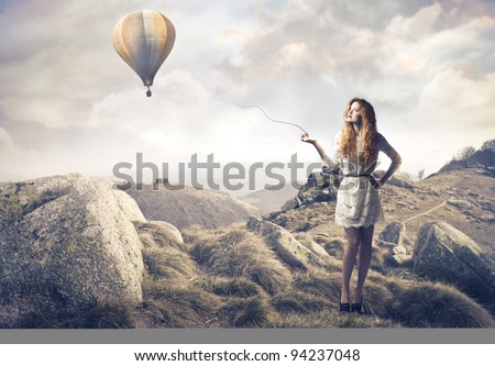 Beautiful woman with hot-air balloon in the background