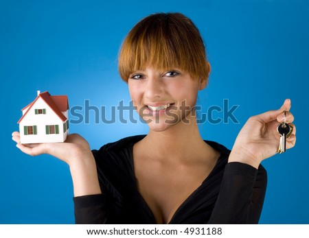 Beautiful woman with house miniature in hand and with keys in other. Smiling and looking at camera. Blue background, front view