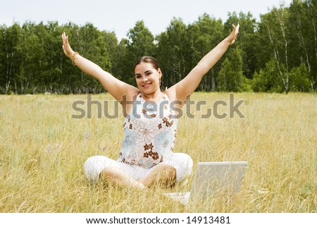 beautiful woman with laptop on the grass