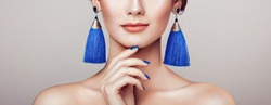 Beautiful woman with large earrings tassels jewelry blue color. Perfect makeup and nails manicure