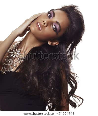 beautiful woman with long black curly hair, tanned skin and dramatic make-up wearing black dress and a flower expensive necklace over white background.