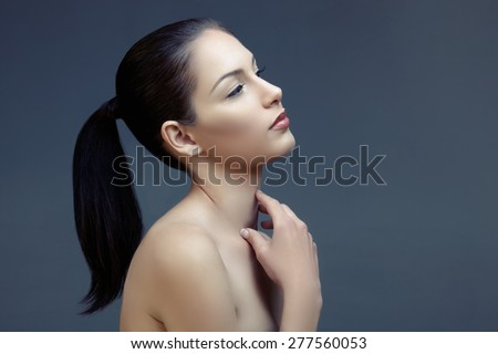 beautiful woman with long black hair in ponytail and shiny skin looking up in profile, natural make-up and beautiful skin texture
