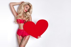 Beautiful woman with long blond hair standing on a white background dressed in red underwear and holds in his hands a red heart Valentine's Day