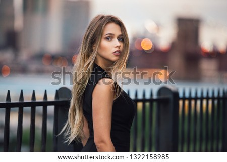 Beautiful woman with long blond hair walking in the city at evening time wearing elegant black dress