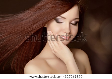 Beautiful woman with long brown hair. Closeup portrait of fashion model posing at studio.