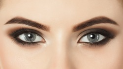 Beautiful woman with long eyelashes and with beautiful evening make-up. Eyes close up. Looking at the camera
