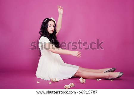 beautiful woman with long glossy hair in pink studio
