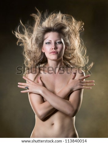 beautiful woman with long golden hair in motion, studio shot