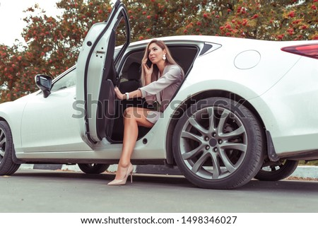 Beautiful woman with long hair gets out of car in summer in city. Concept meeting for an important conference, high heel shoes. VIP taxi, passenger leaves. Mobile phone, an important call for work