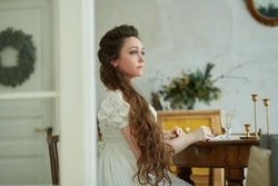 Beautiful woman with long hair in a long white dress. He sits at the vintage table and looks away. Historical reconstruction