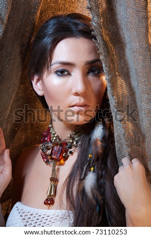 Beautiful woman with long hair looking from tent - studio photo with professional makeup