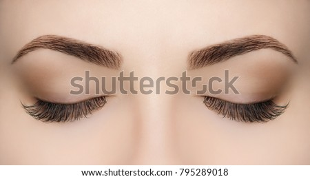 Beautiful Woman with long lashes in a beauty salon. Eyelash extension procedure.  #795289018