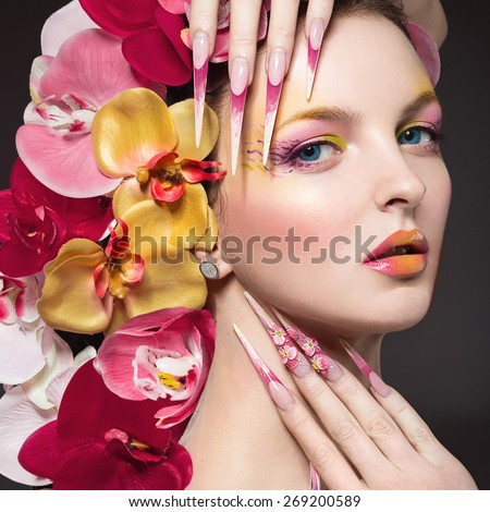 Beautiful woman with long nails, perfect skin, hair of orchids. Portrait shot in the studio.