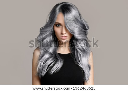 Beautiful woman with long wavy coloring hair. Flat gray background. ストックフォト ©
