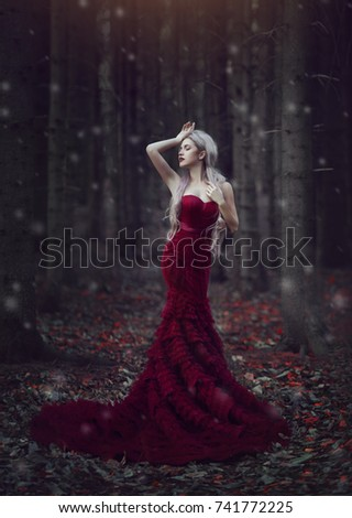 Stock Photo Beautiful woman with long white hair posing in a luxurious red dress with a long train standing in a autumn pine forest. Creative colors and Artistic processing.