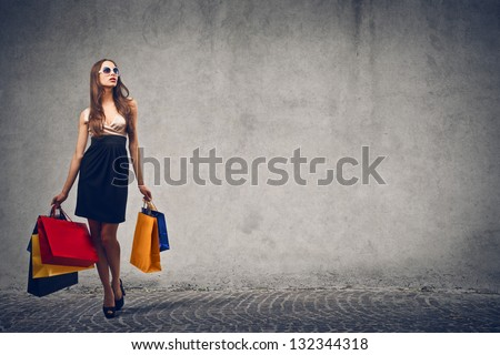 beautiful woman with many shopping bags on gray background