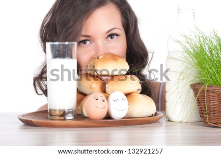 beautiful woman with milk, bun and easter basket of grass.