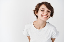 Beautiful woman with natural smooth skin without makeup, posing happy and smiling at camera, standing in t-shirt against white background.