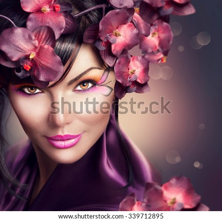 Stock Photo Beautiful Woman with Orchid flower hairstyle and creative makeup. Beauty brunette lady portrait with holiday make-up