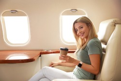 Beautiful woman with paper cup on plane. Air travel