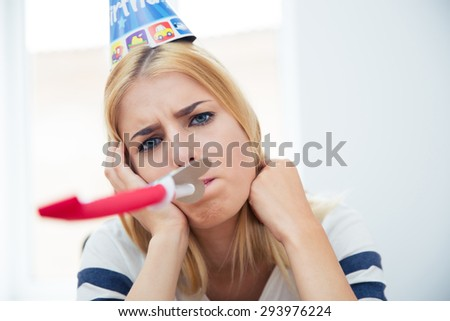 Beautiful woman with party hat and blows whistle