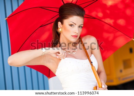 beautiful woman with perfect skin wearing professional make-up holding a red umbrella