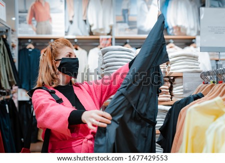 beautiful woman with phone bright pink shopping Mall coat with black protective mask on her face from virus infected air. concept of virus protection in the fashion, beauty, and shopping industries.