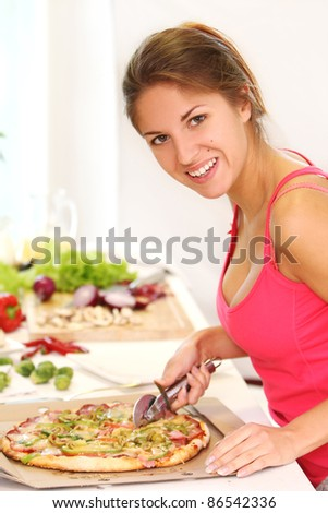 Beautiful woman with pizza on the kitchen