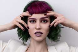 Beautiful woman with purple green professional colored hair. Bright eyes and lips makeup. Fashion girl with short hair and piercing.