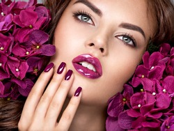 Beautiful  woman with purple make-up of lips and fingernails. Closeup woman's portrait with flowers. Young caucasian gorgeous attractive girl. Model. Vivid make-up. Sexy female. Violet fingernails