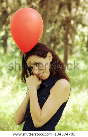 Beautiful woman with red balloon in the park