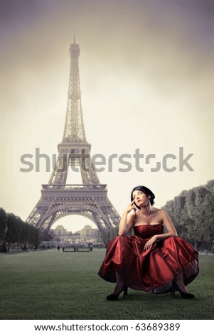 Beautiful woman with red dress and Eiffel Tower on the background