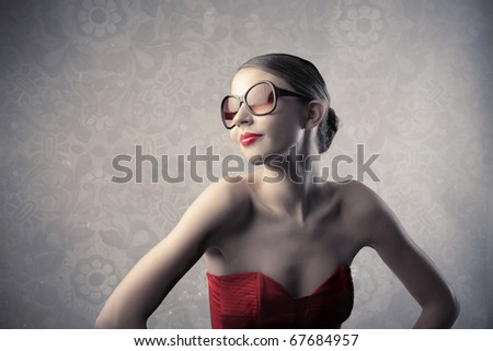 Beautiful woman with red dress and sunglasses - stock photo