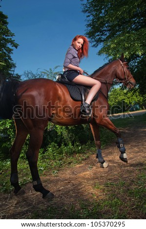 Beautiful woman with red hair sitting on a horse