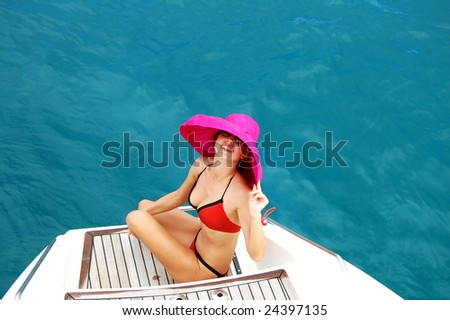 Beautiful woman with red hat on a yacht