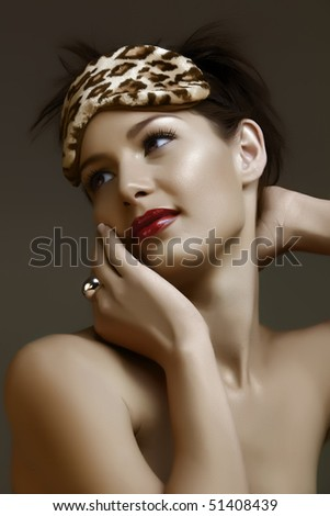 beautiful woman with red lips and leopard print face mask - stock photo