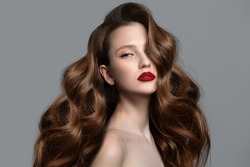 Beautiful woman with red lips and shiny wavy hair. Thick curls and makeup