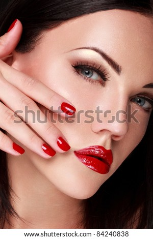 Beautiful Woman With Red Nails and Lips. Makeup and Manicure.