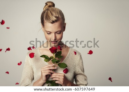Beautiful woman with red rose petals, studio Stock photo ©