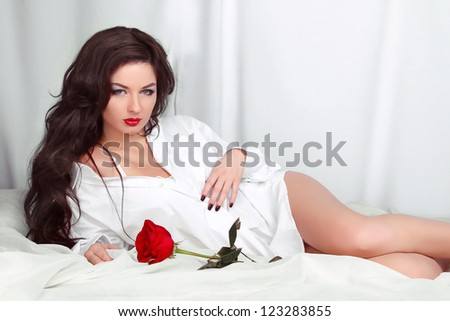 Beautiful woman with red rose posing in shirt lying on the white bed