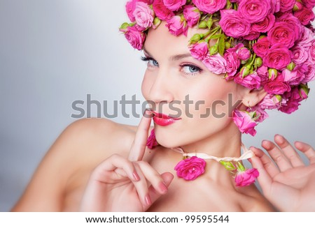Beautiful woman with rose flowers in hair
