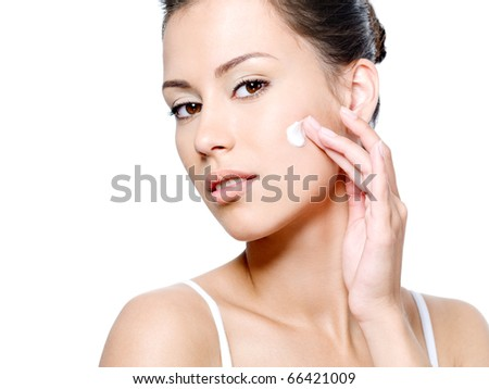 Beautiful woman with sensual look applying cream on her clean face - white background