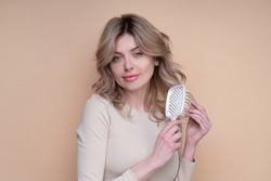 Beautiful woman with shiny hair. Blonde curly hair. Perfect woman with with a comb. Care. Female model after hair procedure. Natural health glance hair on beige background