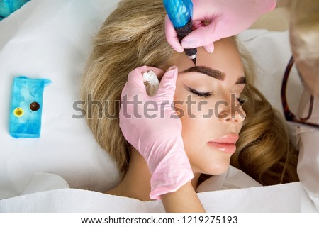 Beautiful woman with smooth, young skin, sitting in a beautician. A beautician performs modeling permanent eyebrows makings.Permanent makeup treatment. #1219275193