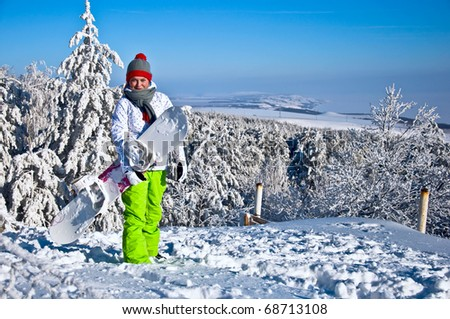 Beautiful woman with snowboard stands on top of the mountain. Against the backdrop of snow-covered pine trees and blue sky.
