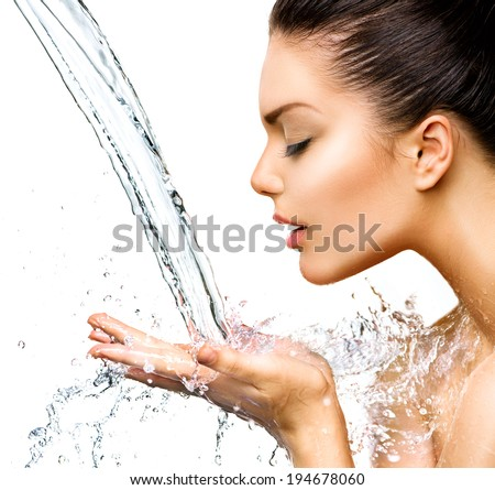 Beautiful Woman with splashes of water in her hands Beautiful Smiling model girl under splash of water with fresh skin over blue background Skin care Cleansing and moisturizing concept Beauty face
