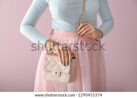 Beautiful woman with stylish bag and jewelry on color background #1290455374