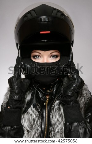 Beautiful woman with stylish makeup in black biker helmet, mask and gloves