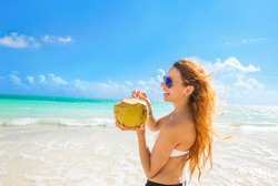 Beautiful woman with sunglasses on a tropical beach enjoying ocean sea view, taking deep breath